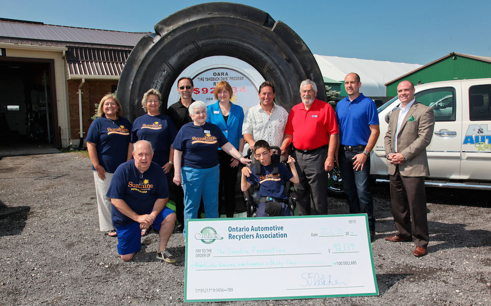 Representatives from The Sunshine Foundation, Ontario Tire Stewardship, and Ontario Automotive Recyclers Association celebrate at A&L Auto Recyclers in Comber, Ontario. The 2014 Tire Take Back event raised over $90,000 for The Sunshine Foundation. Photo credit: Trevor Booth.